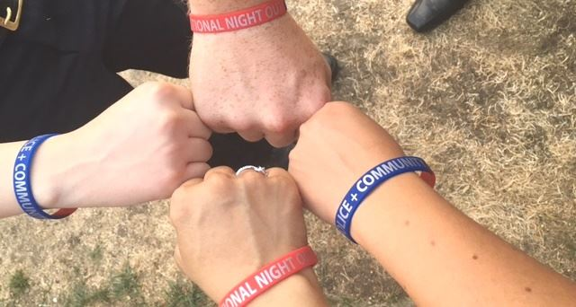 Photo of fists touching with bracelets for National Night Out and Community + Police