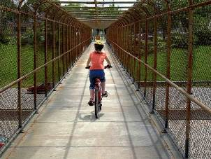 Person riding a bike over a bridge