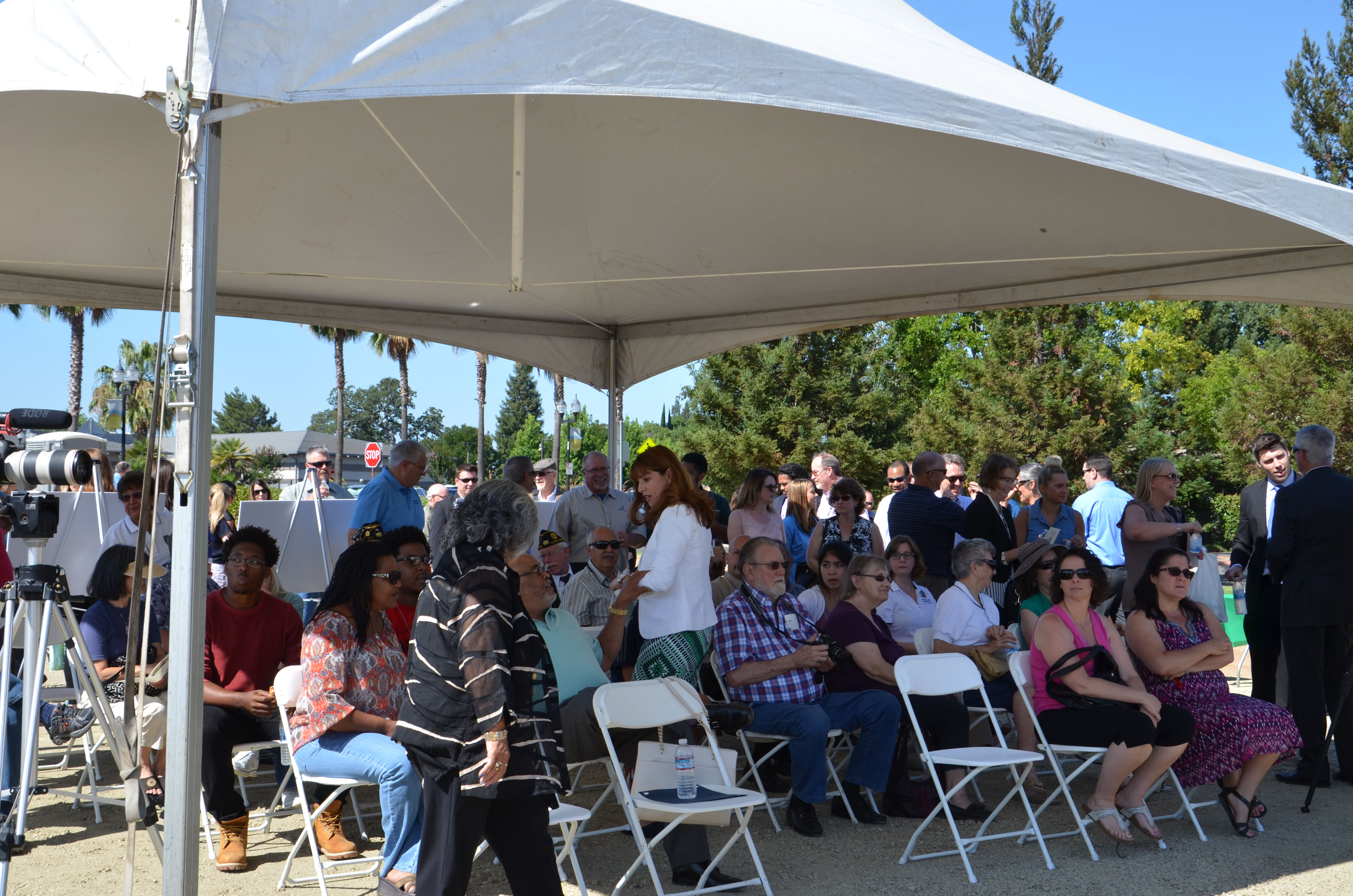 The community gathers under a tent for the ceremony